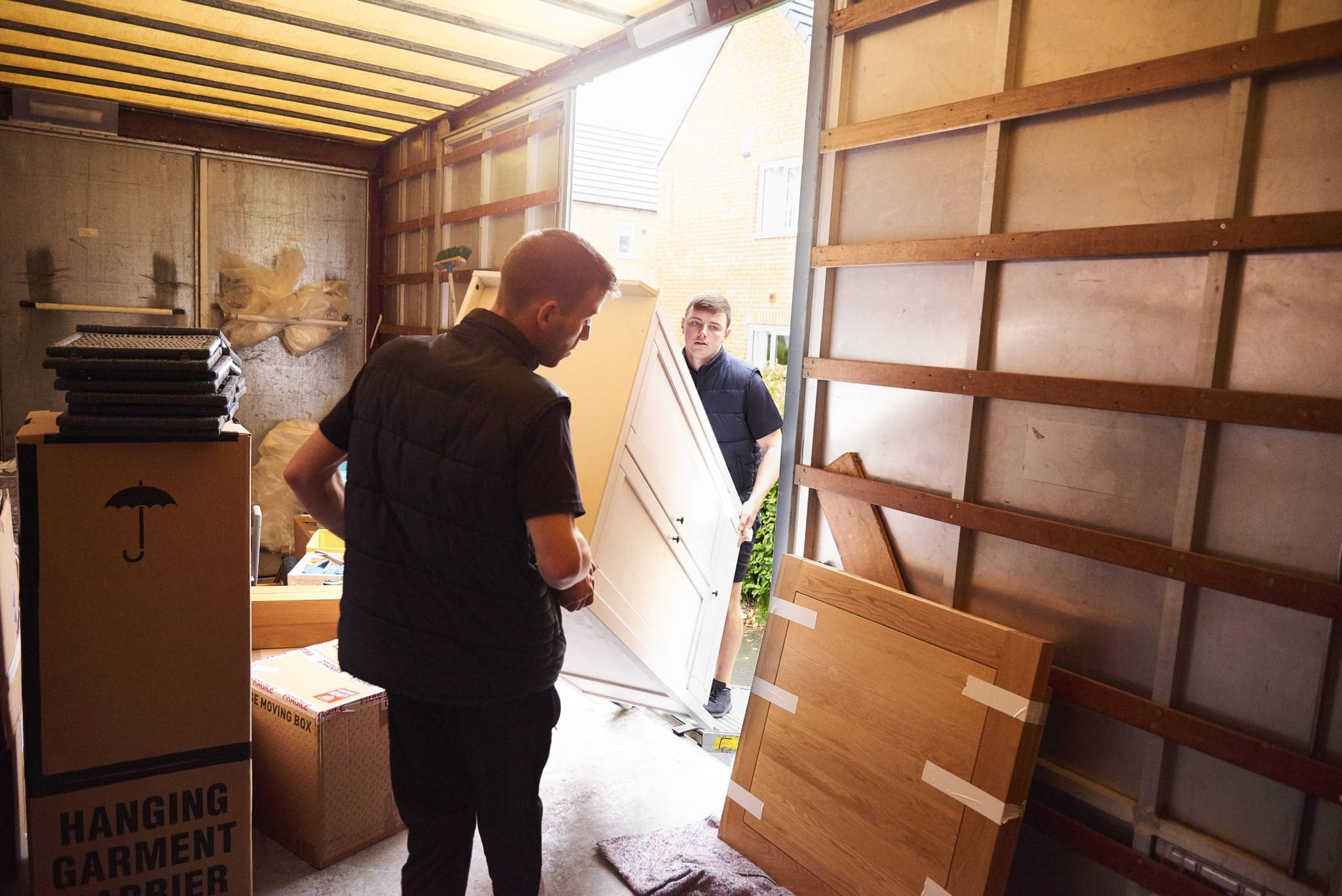 two movers putting boxed inherited belongings in a moving truck