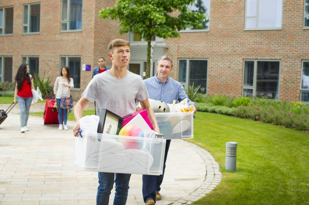 parent and child carrying boxes to a college dorm