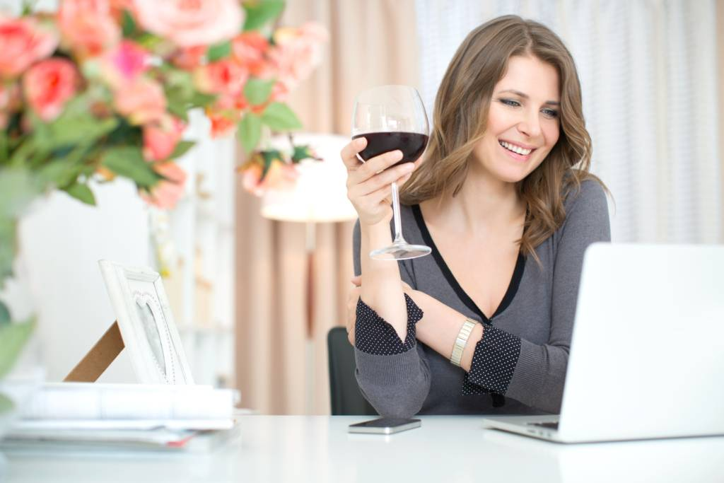 woman attending a virtual Colorado event while drinking wine